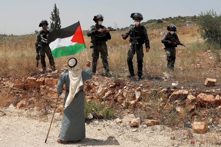 Image: A demonstrator holds a Palestinian flag in front of Israeli forces during a protest against Israel's plan to annex parts of the occupied West Bank