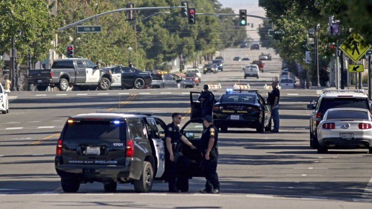 Image: Law enforcement personnel from several jurisdictions patrol Spring Street in downtown Paso Robles, Calif