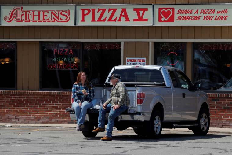 Image: Jim and Marilyn Ridel eat their take out lunch in the parking lot outside the restaurant amid the coronavirus disease (COVID-19) outbreak in Keene, New Hampshire