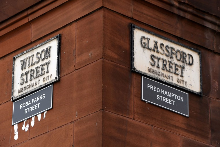 Image: Signs renaming Wilson Street as Rosa Parks Street, the American activist in the civil rights movement,and Glassford Street as Fred Hampton Street, the American activist and revolutionary socialist, are displayed in the Merchant City area of Glasgow