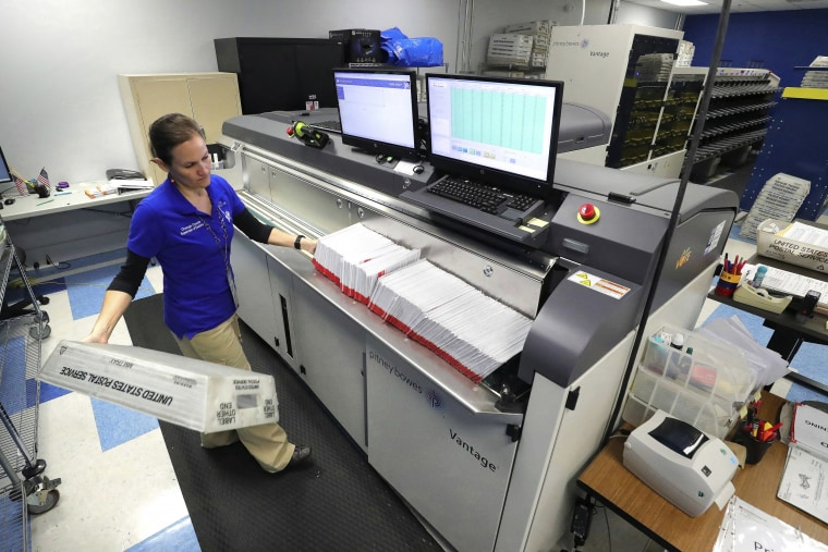 A worker processes mail-in ballots for the state's primary elections at the Orange County Supervisor of Elections office in Orlando, Fla., on March 17, 202.