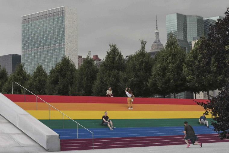 With the U.N. headquarters in the background, visitors take photos at the FDR Four Freedoms State Park's monumental stair, transformed into a giant, rainbow-hued LGBTQ flag in celebration of World Pride on June 17, 2019, on Roosevelt Island, N.Y.