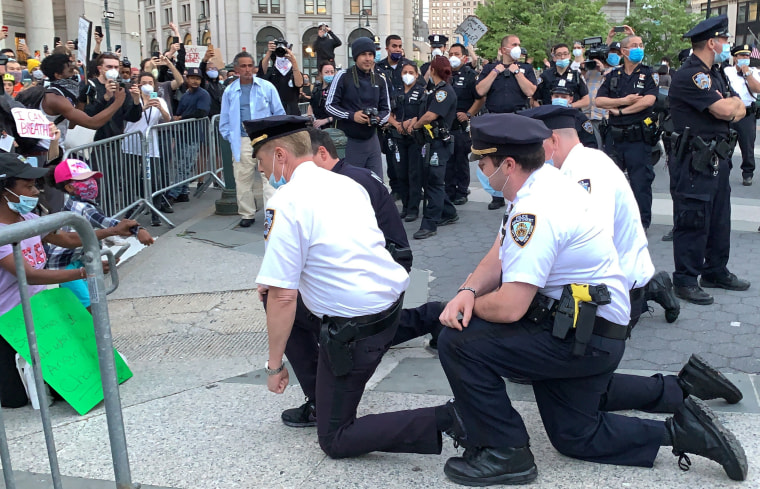 Lt. Robert Cattani, foreground right, takes a knee in New York City's Foley Square on May 31, 2020.