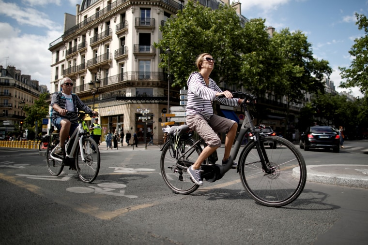 Image: A woman rides a bicycle as France eases lockdown measures on June 14, 2020.