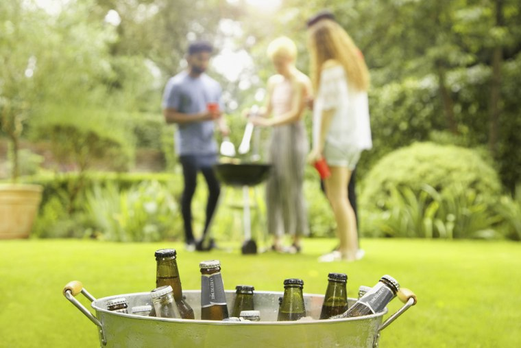 Beer bottles in bucket while friends enjoying barbecue party in background at yard