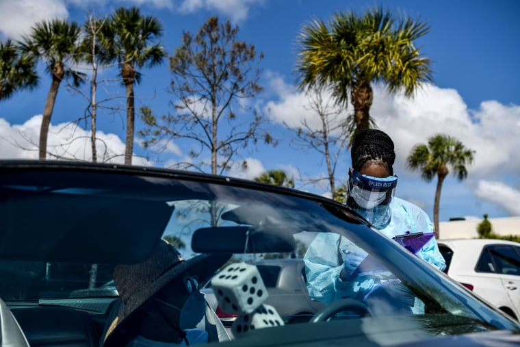 Image: A medical worker fills out a form while speaking to a driver at a drive-thru coronavirus testing lab in West Palm Beach, Fla., on March 16, 2020.