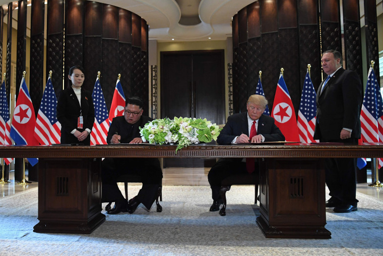 Image: President Donald Trump and North Korea's leader Kim Jong Un sign documents as Secretary of State Mike Pompeo and the North Korean leader's sister Kim Yo Jong look on
