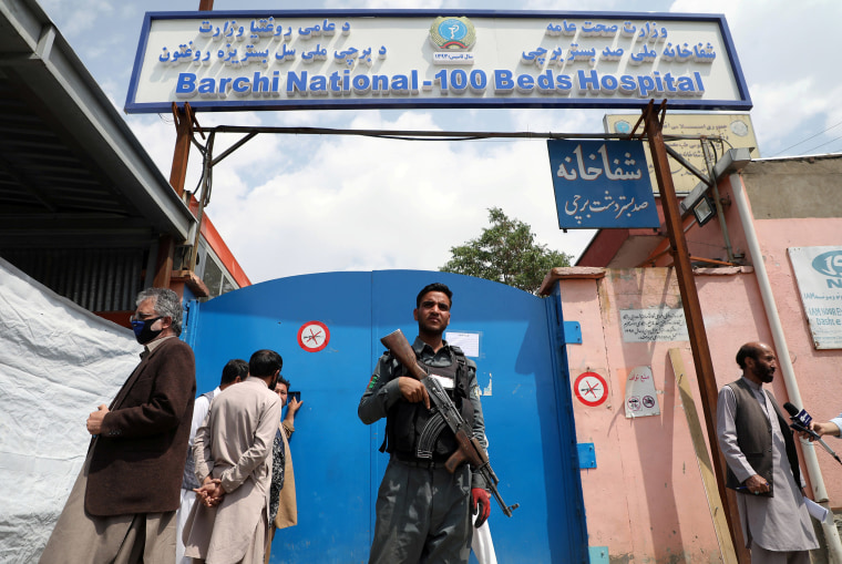 Image: An Afghan policeman keeps watch outside of a hospital which came under attack in Kabul, Afghanistan