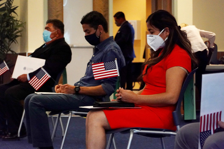 Image: Giagnna Mendez, originally from Peru, wearing a mask to protect against the coronavirus participates in a swearing in ceremony to become an American citizen held at the U.S. Citizenship and Immigration Service's Kendall office
