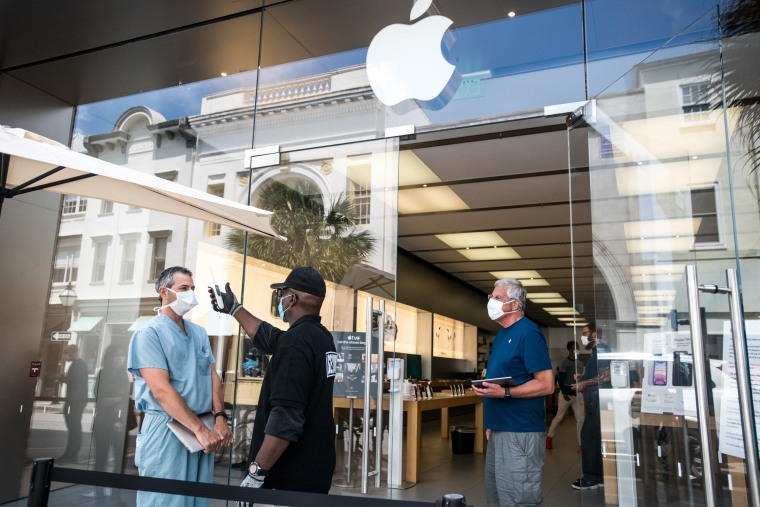 Image: A security guard takes the temperature of a customer outside the Apple store in Charleston