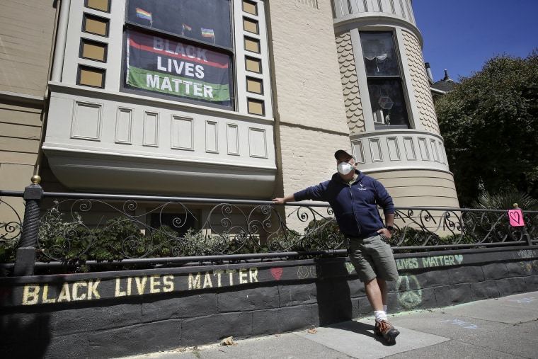 Image: James Juanillo stands next to a chalk message outside of his home in San Francisco on June 14, 2020.