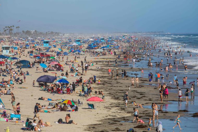 Image: People at the beach amid the coronavirus pandemic in Huntington Beach, Calif.