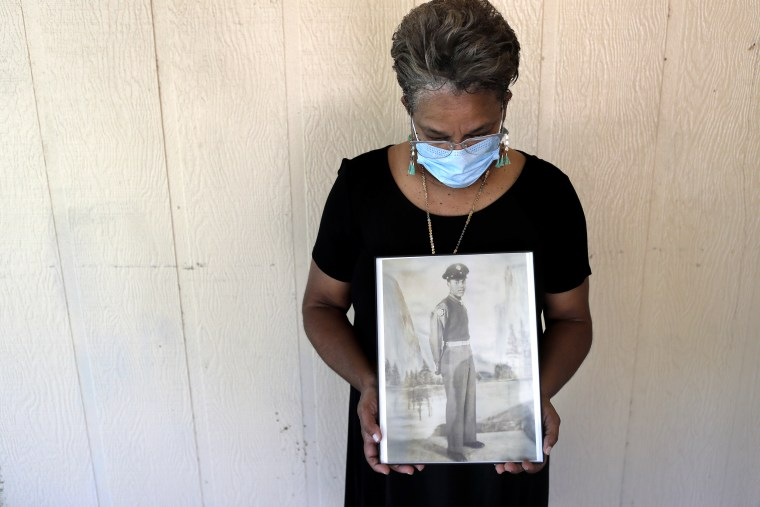 Belvin Jefferson White poses with a portrait of her father Saymon Jefferson at Saymon's home in Baton Rouge, La. on May 18, 2020. Belvin recently lost both her father and her uncle, Willie Lee Jefferson, to COVID-19.