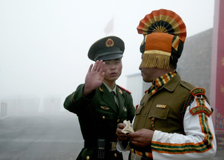 Image: A Chinese soldier gestures as he stands near an Indian soldier on the Chinese side of the ancient Nathu La border crossing between India and China.