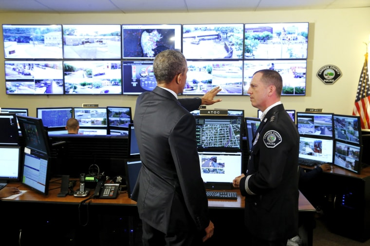 Obama speaks with Thomson as he tours the Camden County Police Department's Real-Time Tactical Operational Intelligence Center in Camden, New Jersey