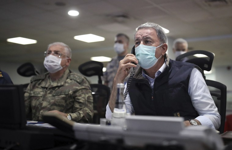 Image: Turkish Defense Minister Hulusi Akar, right, and Chief of Staff Gen. Yasar Guler wearing face masks to protect against the coronavirus, monitor the operation at a military headquarters in Ankara, Turkey