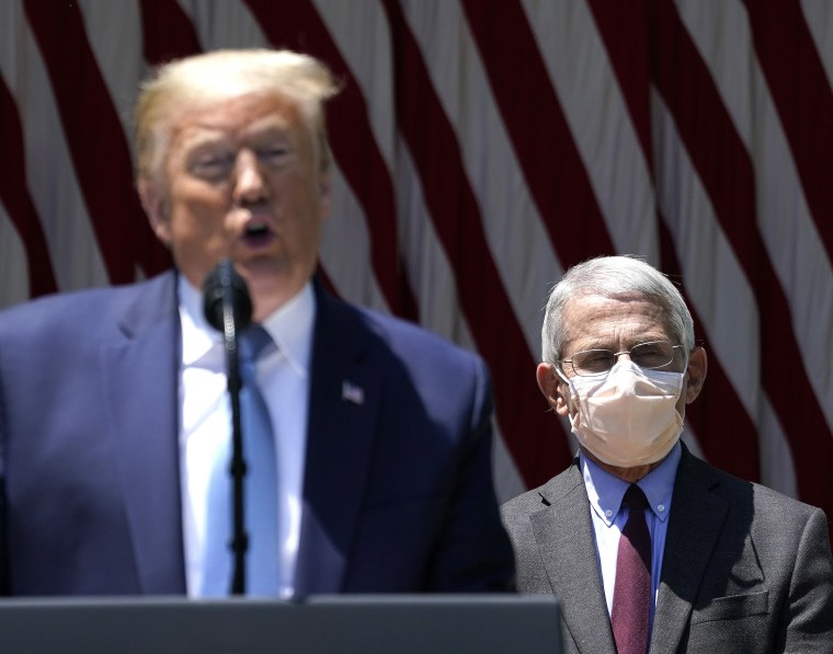 Image: President Donald Trump is flanked by Dr. Anthony Fauci while speaking about coronavirus vaccine development in the Rose Garden of the White House.