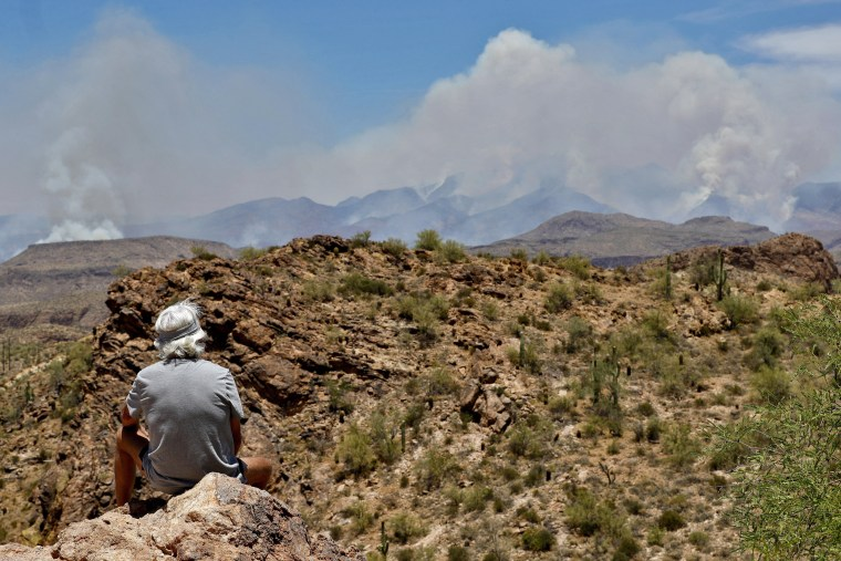 Image: A man watches a portion of the Bush fire burn through the Tonto National Forest from Apache Junction, Ariz.