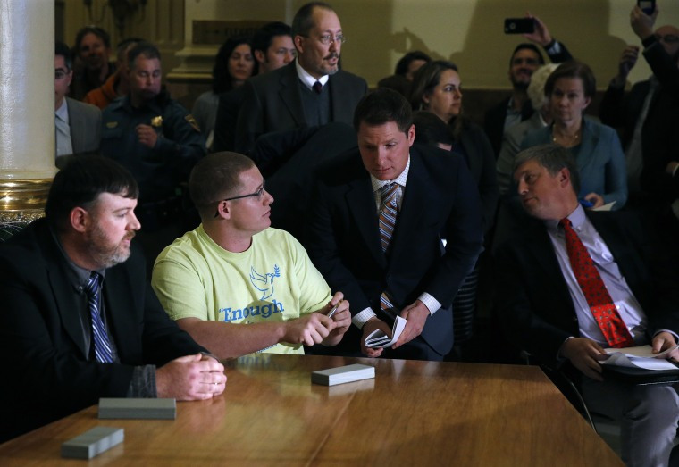 Image: Colorado elector Micheal Baca, second from left, talks with legal counsel after he was removed from the panel for voting for a different candidate than the one who won the popular vote