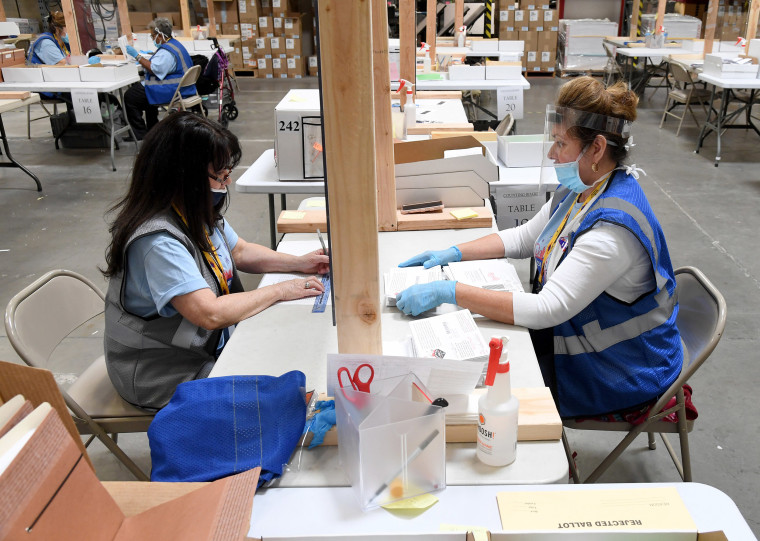 Image: Ann-Marie Gomes (L) and Juanita Thompson count and verify mail ballots at the Clark County Election Department, which is serving as both a primary election ballot drop-off point and an in-person voting center amid the coronavirus pandemic on June 9