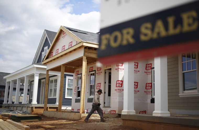 """A contractor walks past a \""""For Sale\"""" sign while working on a home in Louisville, Ky."""
