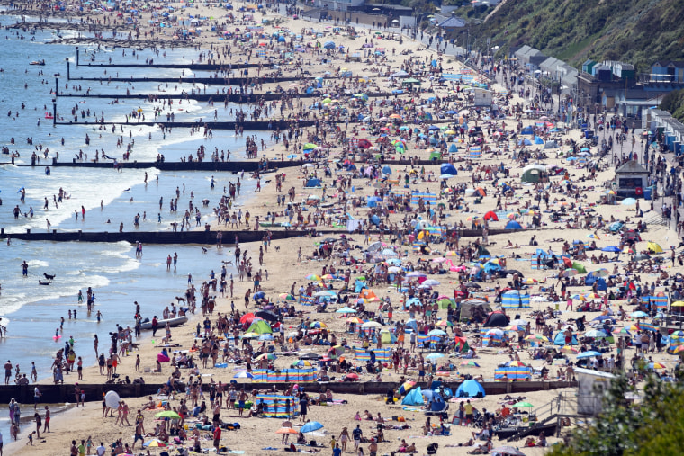 Image: Tourists enjoy the hot weather at the beach in Bournemouth