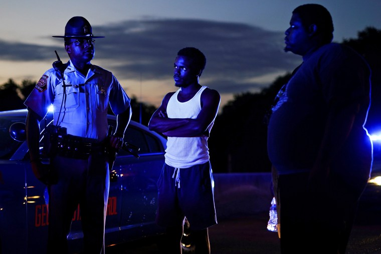 Image: Two protesters speak with a Georgia State Patrol officer after taking over and blocking a freeway during a rally against racial inequality and the police shooting death of Rayshard Brooks, in Atlanta