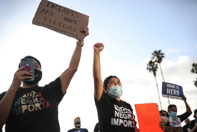 Image: People hold signs and a woman raises her fist during a rally in support of the Supreme Court's ruling in favor of the Deferred Action for Childhood Arrivals (DACA) program, in San Diego, California
