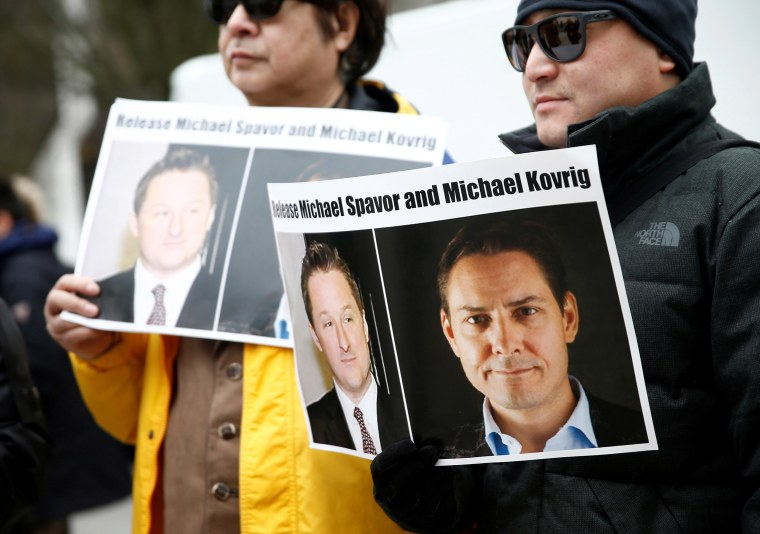 Image: People hold signs calling for China to release Canadian detainees Spavor and Kovrig during an extradition hearing for Huawei Technologies Chief Financial Officer Meng Wanzhou at the B.C. Supreme Court in Vancouver