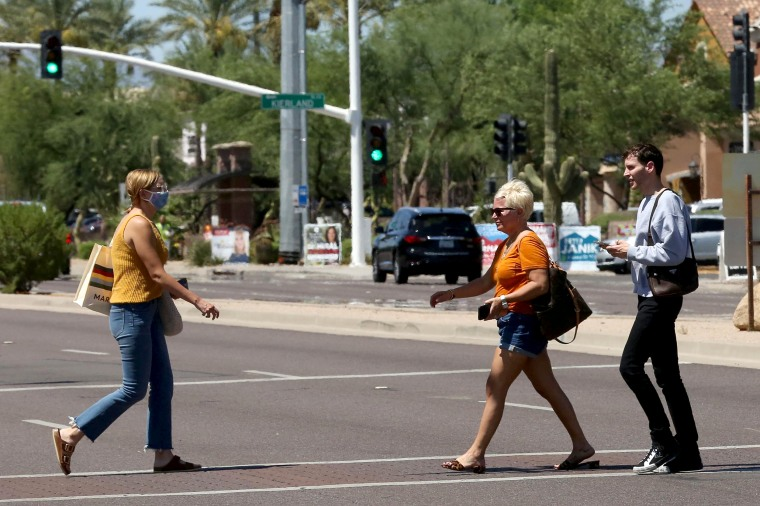 Image: People cross the street between Kierland Commons and Scottsdale Quarter with and without face coverings, during the global outbreak of the coronavirus disease (COVID-19), in Scottsdale
