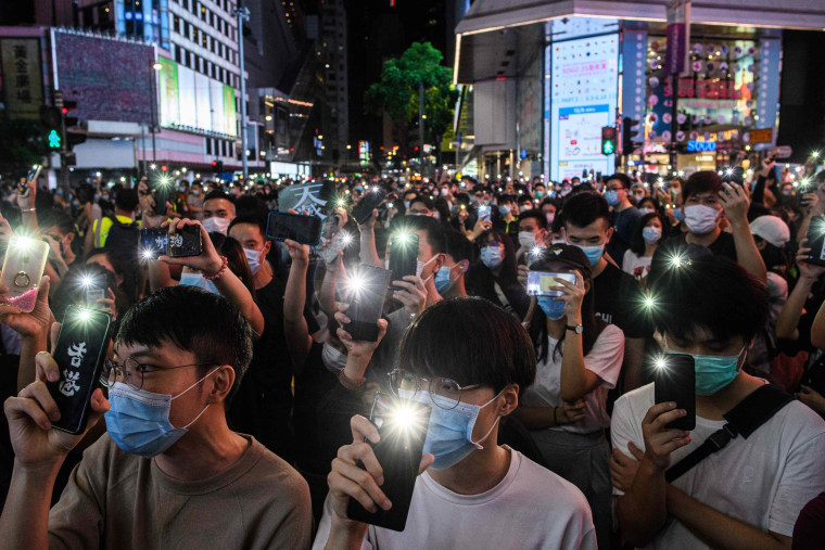 Pro-democracy activists hold up their mobile phones during a rally in the Causeway Bay district of Hong Kong on June 12, 2020.