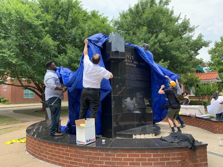 Residents of Greenwood community wrap the 1921 Tulsa Massacre Memorial in a blue tarp in advance of a possible visit by Vice President Mike Pence.