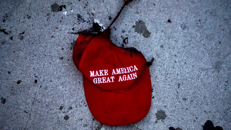 Image: A burnt Make America Great Again hat after a protest outside of a campaign rally held by President Donald Trump in Tulsa, Okla., on June 20, 2020.