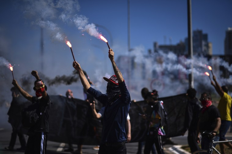 Demonstrators hold flares during a protest against racism, the policies of President Jair Bolsonaro's government, and to defend democracy amid the coronavirus pandemic in Brasilia, Brazil on Sunday.