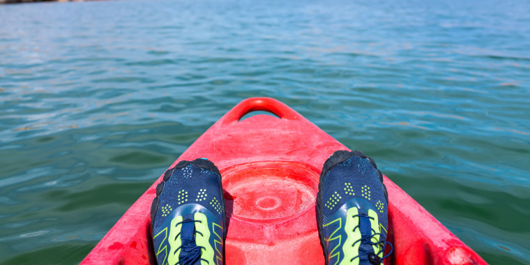 Kayaking in Lake Powell to antelope canyon with feet water shoes at front of red kayak boat and blue turquoise water