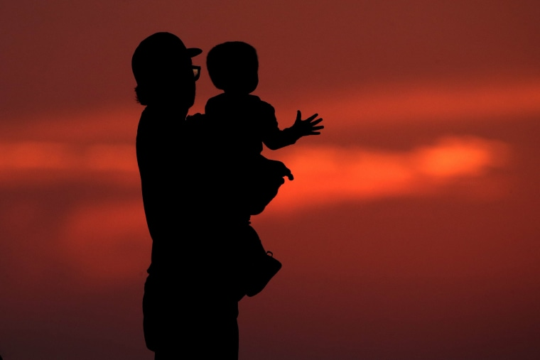 A man and his son are silhouetted against the sky as they watch the sunset from a park in Kansas City, Mo., Friday, June 26, 2020. Sunsets and sunrises are more vibrant than usual lately due to dust in the atmosphere from a Saharan dust cloud.