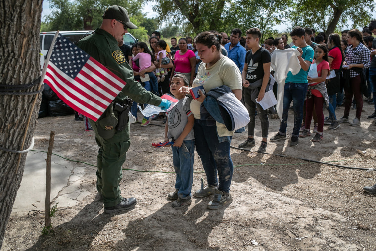 Image: A U.S. Border Patrol agent gathers personal effects from immigrants before they were transferred to a McAllen processing center on in Los Ebanos, Texas.