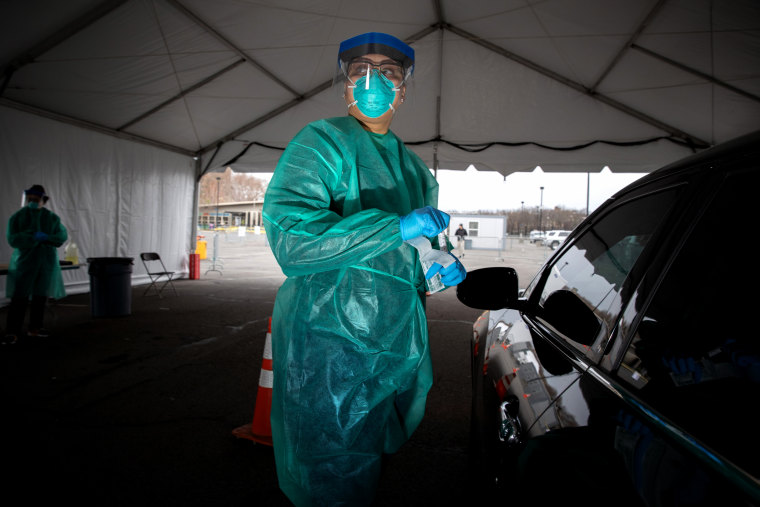 Image: A doctor waits to test a patient at a drive-thru coronavirus testing center at Lehman College in the Bronx on March 28, 2020.