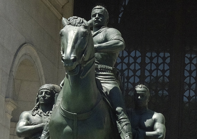 A statue of President Theodore Roosevelt on a horse with an Indigenous person walking alongside him on his right and an African on his left side near the entrance to the Museum of Natural History in New York.