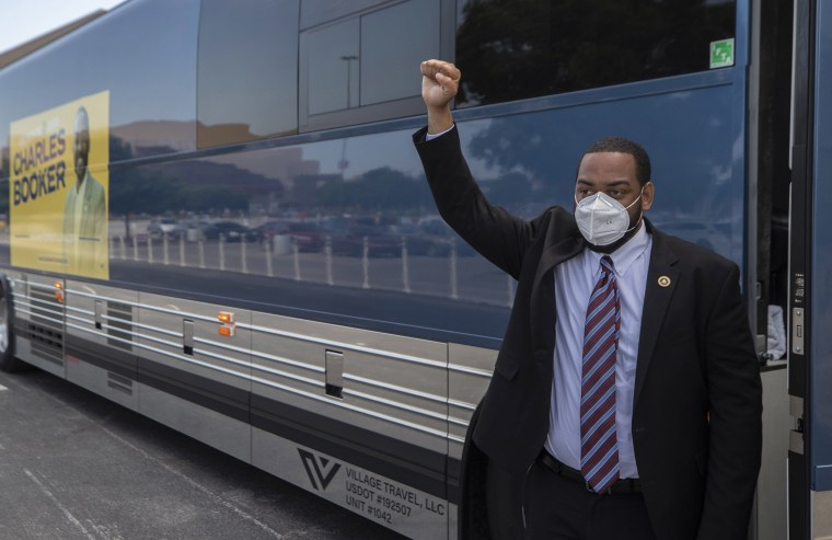 Image: Charles Booker a Democratic candidate for the U.S Senate raises before voting at the Kentucky Expo Center