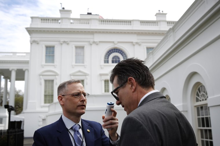 Image: A member of the White House physicians office takes the temperature of a member of the media on March 21, 2020.