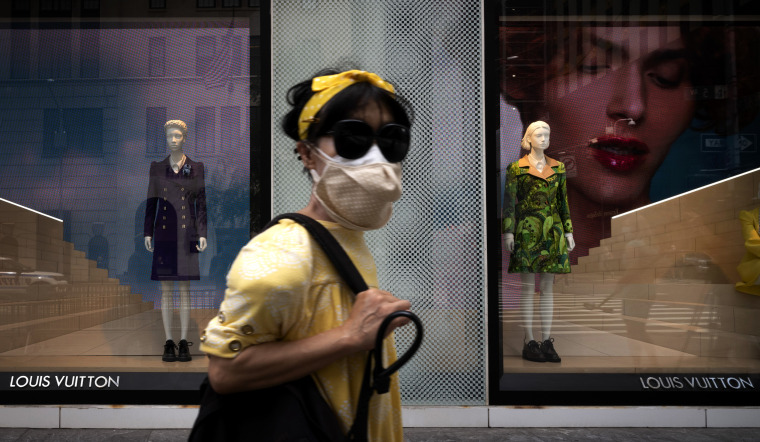 Image: A woman wearing a mask passes by a Louis Vuitton store on New York's Fifth Avenue on June 11, 2020.