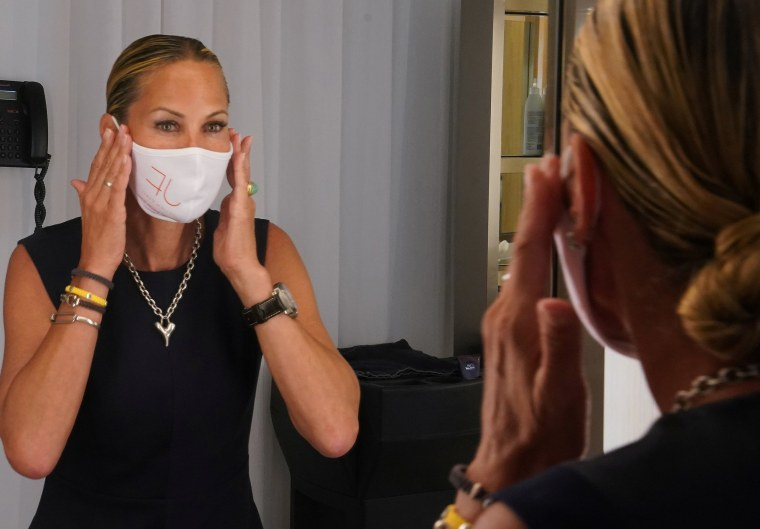 Image: Suelyn Farel adjusts her mask on the first day of the phase two re-opening of businesses following the outbreak of the coronavirus disease (COVID-19), in the Manhattan borough of New York City