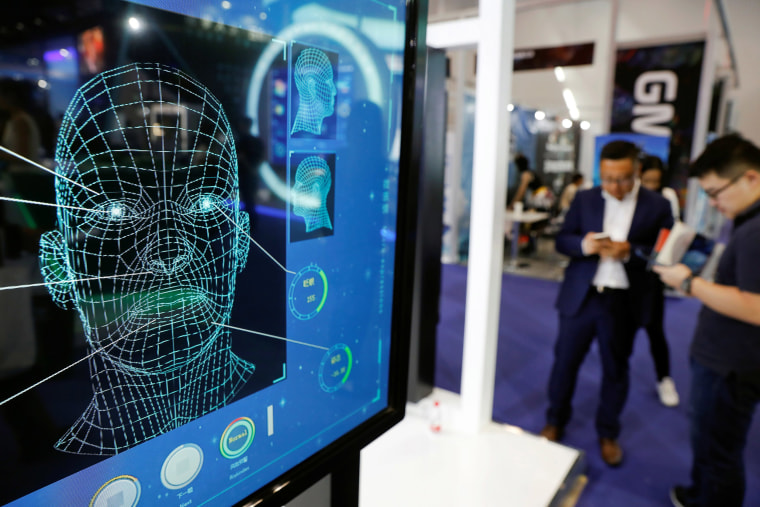 Image: Visitors check their phones behind the screen advertising facial recognition software during Global Mobile Internet Conference (GMIC) at the National Convention in Beijing