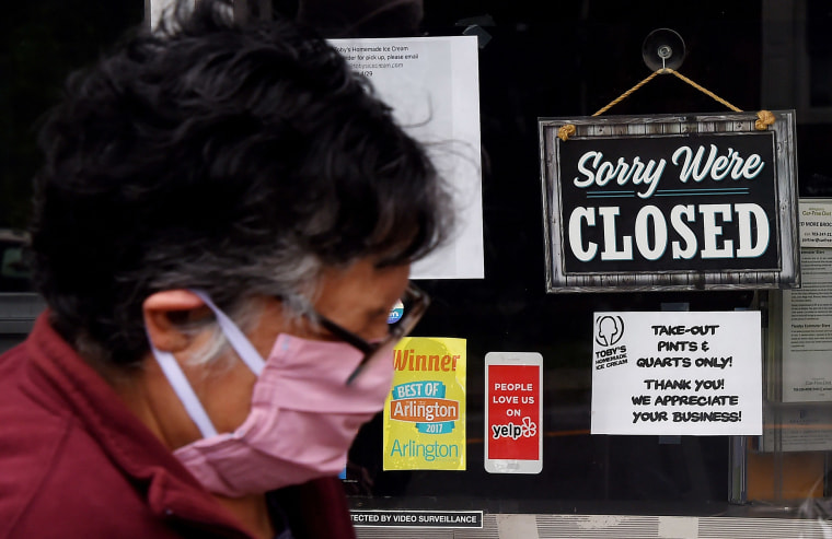 Image: A woman wearing a face mask walks past a sign in the window of a food store announcing that the business is closed during a shelter in place lockdown order during an outbreak of COVID-1 in Arlington