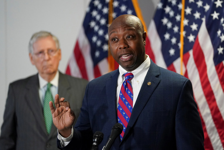 Image: Senate Majority Leader Mitch McConnell (R-KY) listens as Sen. Tim Scott (R-SC) speak to reporters after the Senate Republicans weekly policy lunch