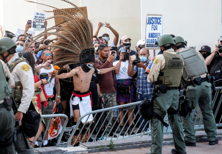 Image: Demonstrators confront Los Angeles County sheriff's deputies in a protest in Compton