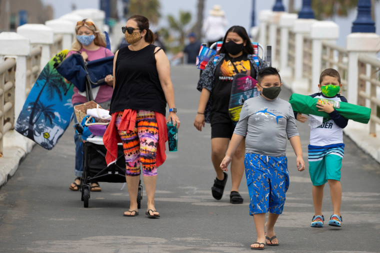 Image: People wear face masks as they arrive at the beach in Oceanside, California
