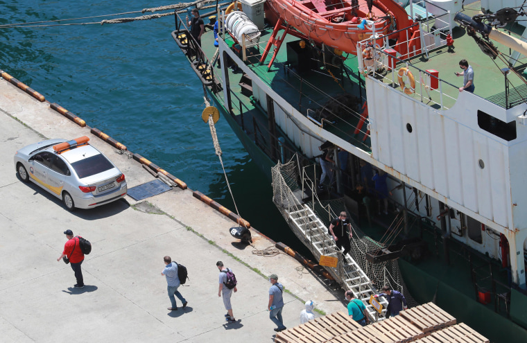 Image: Sixteen crewmen, who have tested positive for the coronavirus, disembark from a Russian refrigerator ship at Gamcheon Port in Busan, South Korea