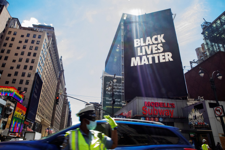 Image: A New York Police Department traffic officer gestures under a large Black Lives Matter banner in New York City, New York